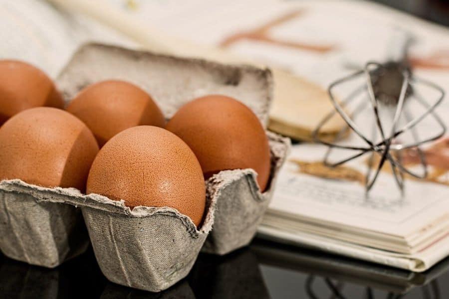 a carton of brown eggs and a mixer