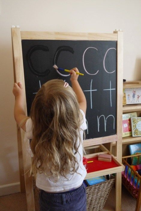 little girl using a paint brush to remove chalk letters from the chalkboard - water activities