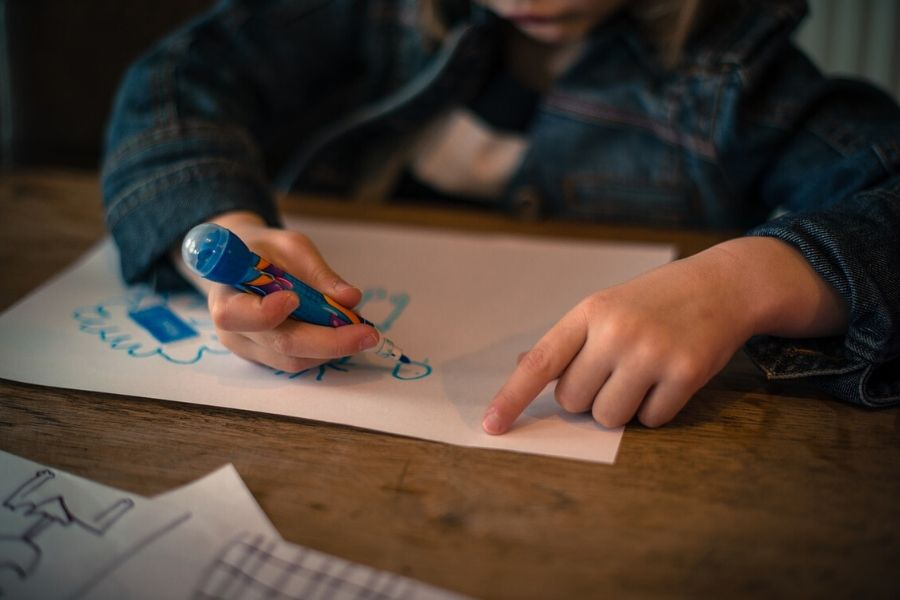 little girl drawing on a sheet of paper with a blue marker
