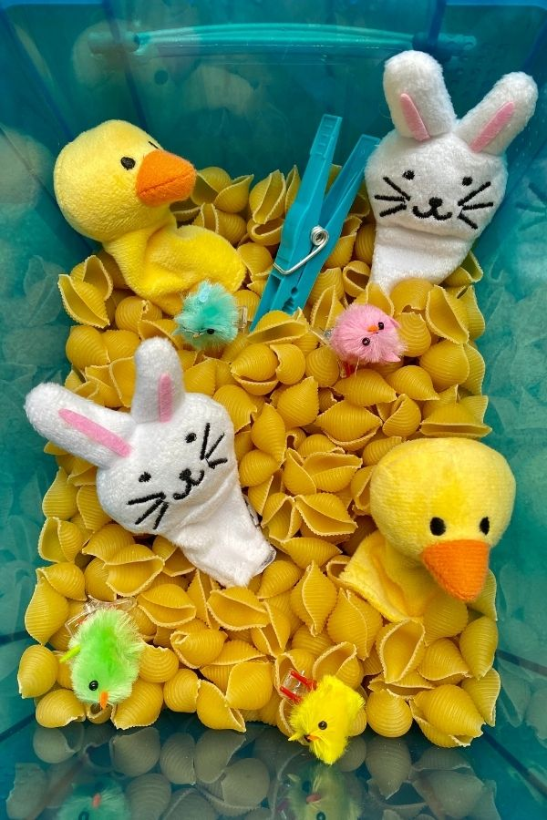 Easter sensory bin filled with dried pasta, rabbits, ducks and chicks