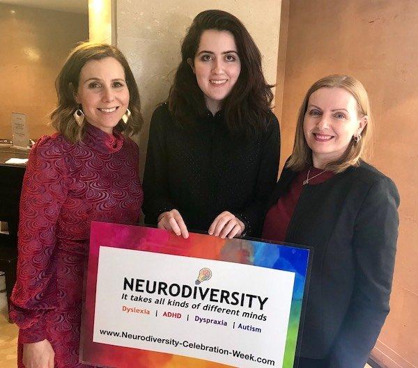 Sally Phillips, Siena Castellon and Tania Tirraoro with Siena holding her Neurodiversity Celebration Week sign