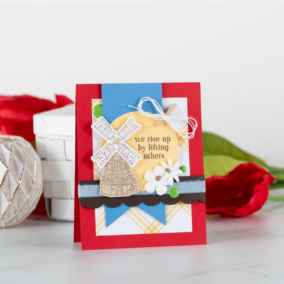 We Rise By Lifting Others handmade card with red, blue and yellow. Dutch Windmill and flowers make this a darling card for springtime.