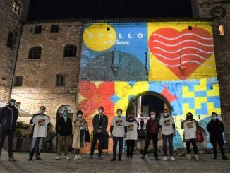 """Porta Consolare illuminata con i colori dell'iniziativa di beneficenza """"Spello nel cuore"""""""