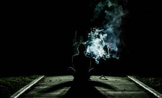 silhouette of man meditating on dark path surrounded by smoke