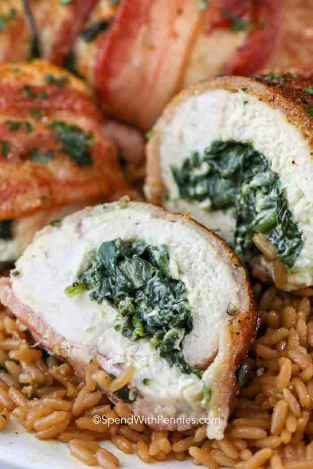 Sliced stuffed chicken breasts full of spinach and cheese on a bed of rice.