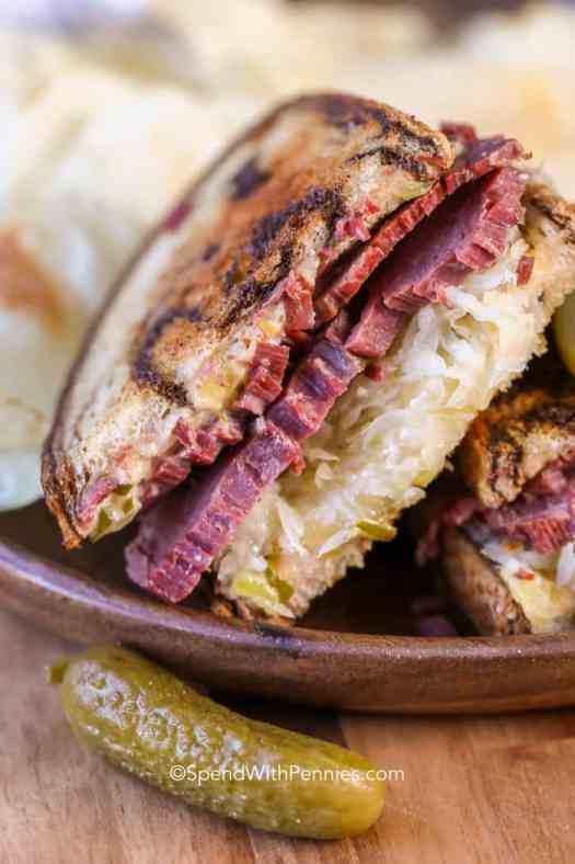 A stacked reuben sandwich on a wooden plate with a pickle next to it.