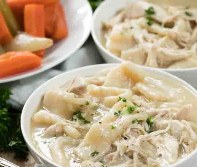 Chicken And Dumplings In A White Bowl With Veggies In The Background