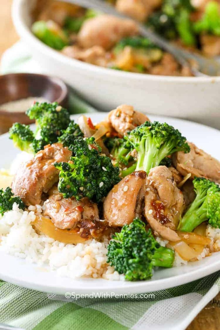 Chicken and Broccoli Stir Fry served over rice on a white plate