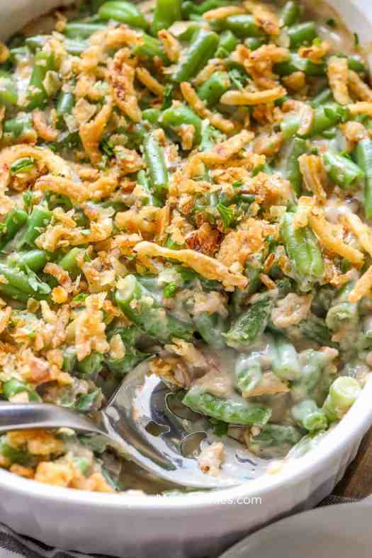 A scoop of green bean casserole full of crispy fried onions and creamy sauce.