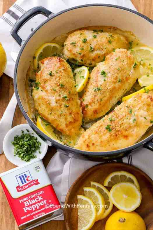 Lemon Pepper Chicken in a skillet garnished with parsley and lemon slices