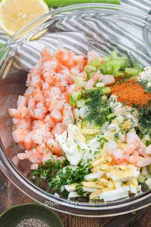 A clear mixing bowl full of shrimp salad ingredients like shrimp, eggs, celery, and dill.