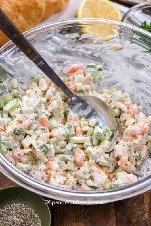 A mixing bowl of shrimp salad with a metal mixing spoon.