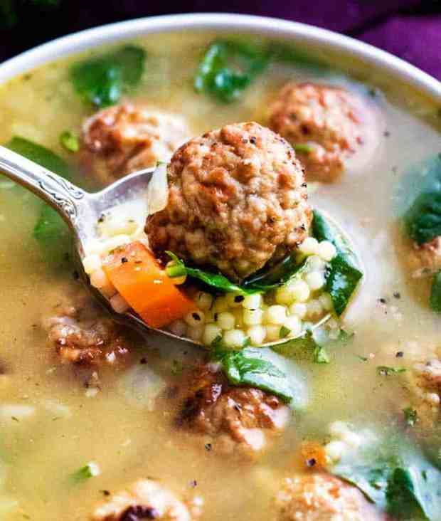 Closeup of apoonful of Italian wedding soup with a bowl of soup in the background