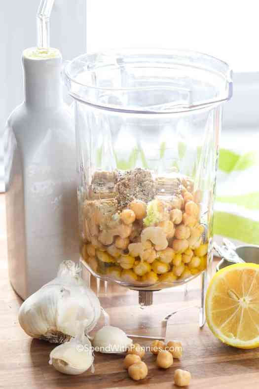 Hummus ingredients in a blender like garbanzo beans, garlic, lemon, and spices.