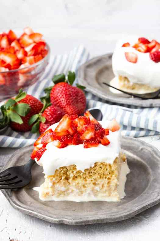 Tres leches cake with strawberries on a grey plate, with a bowl of cut up strawberries on the side