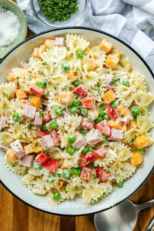 A white serving bowl full of bow tie pasta salad with ham, cheddar and red peppers