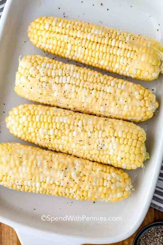 Corn cobs brushed with butter, seasoned and lined up in a baking tray.