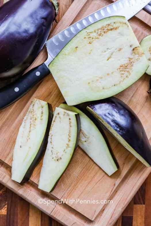 Eggplant being sliced on a cutting board.