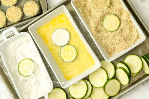 Zucchini slices being dipped in flour, an egg mixture, and then breaded.
