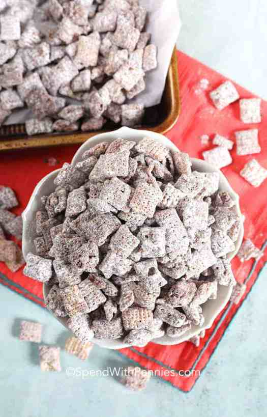 Overview of Puppy Chow in a bowl with muddy buddies on a tray in the background