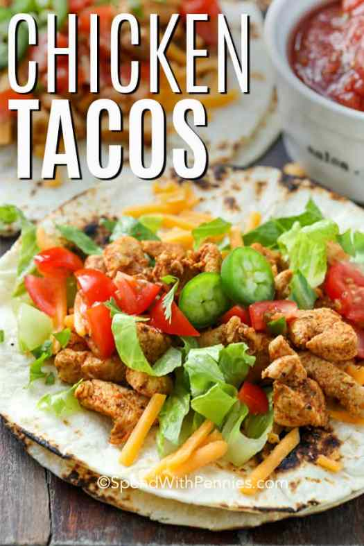A chicken taco on laying open and topped with cheese, jalapenos, lettuce and tomatoes.