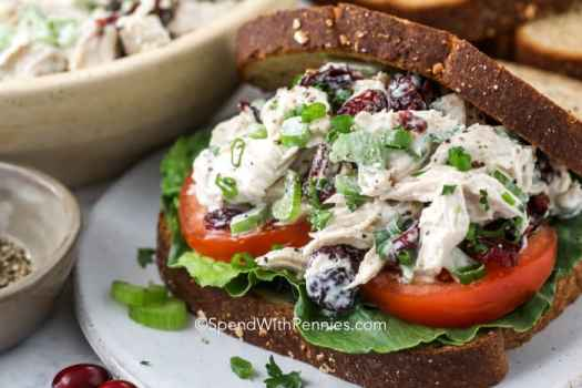 A turkey salad sandwich with lettuce and tomatoes.