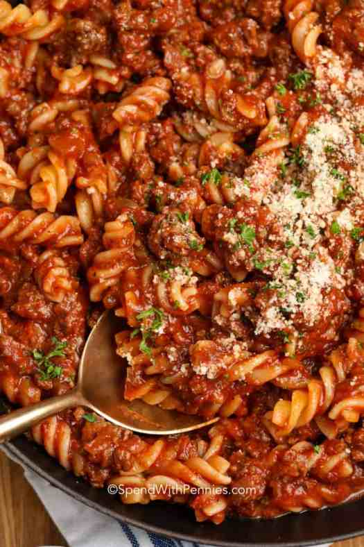 A serving spoon of fusilli with meat sauce topped with parmesan cheese