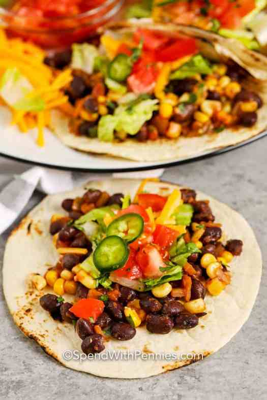A tortilla topped with black bean mixture, lettuce, tomatoes, cheddar cheese, and jalapenos.