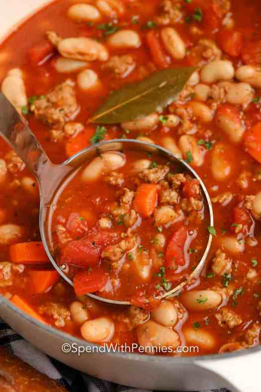 Italian Bean Soup being scooped out of a pan with a ladle.