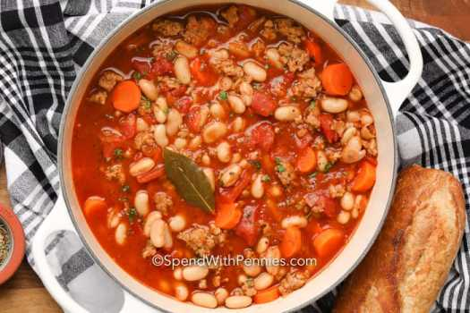 Italian Bean Soup in a pan with a bay leaf, with bread on the side.