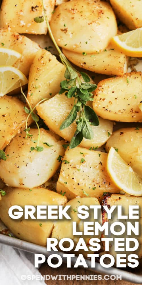 Greek Style Lemon Roasted Potatoes on a baking sheet with thyme and lemon wedges with writing