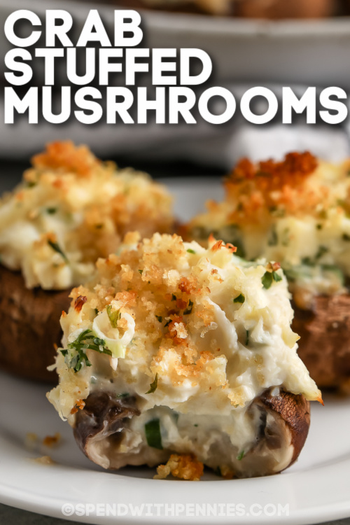 Three crab stuffed mushrooms on a plate with text.