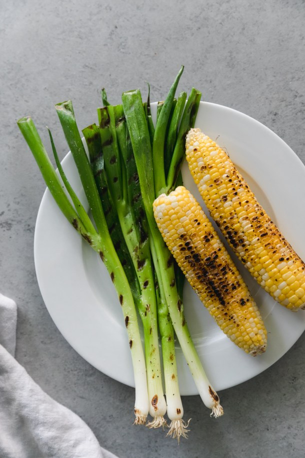 Overhead shot of a plate of grilled scallions and grilled corn