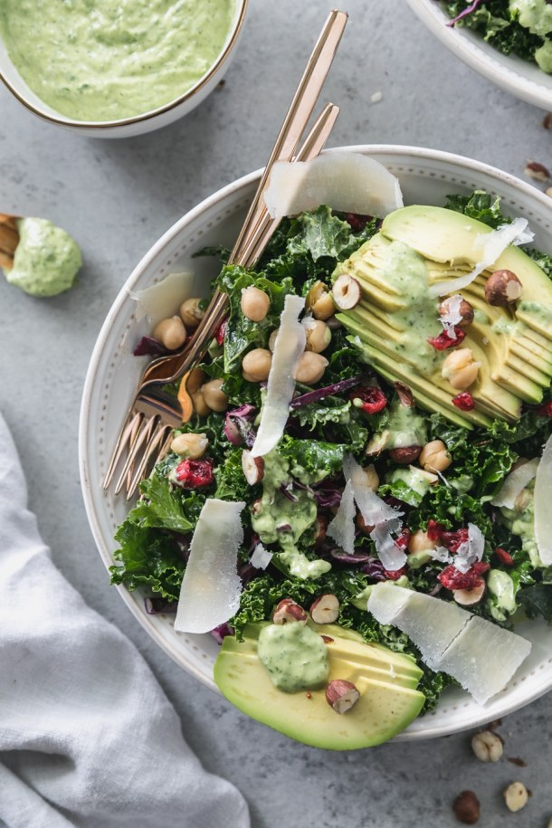 Overhead close up shot of a kale salad topped with sliced avocado, parmesan shavings, hazelnuts, chickpeas, and dried cranberries with a gold fork resting in the bowl