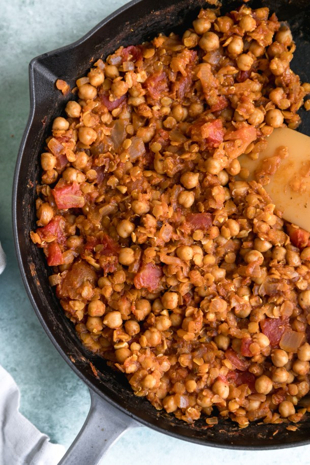 Overhead shot of a cast iron skillet filled with stewed tomatoes, chickpeas, and lentils