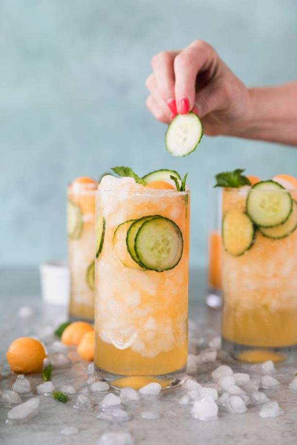 Forward facing shot of 3 cucumber melon cocktails with a hand getting ready to put a sliced cucumber in the closest one