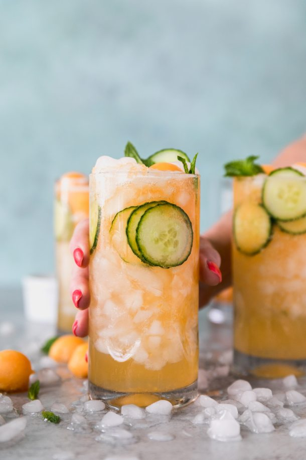 Forward facing shot of 3 cucumber melon cocktails with a hand reaching out and holding the closest one