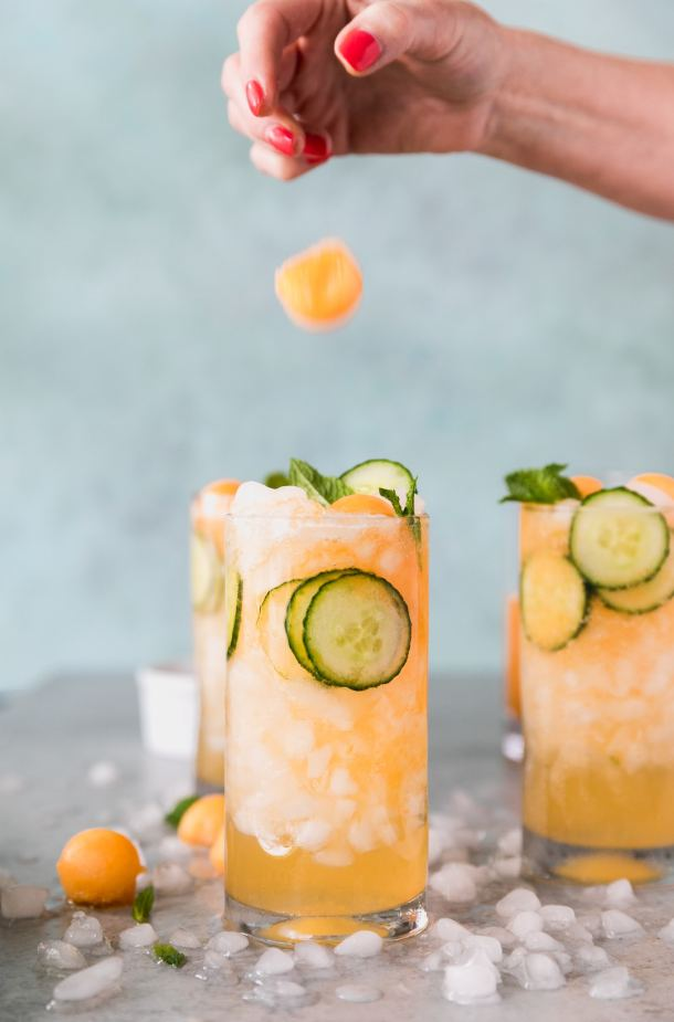 Forward facing shot of 3 cucumber melon cocktails with a hand dropping a melon ball onto the closest one in the foreground