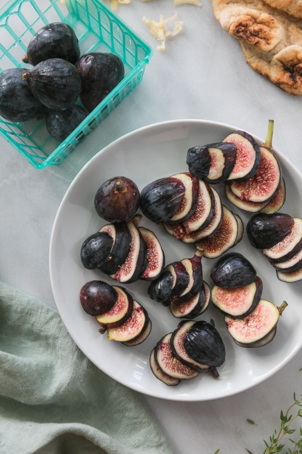 Overhead close up shot of a plate of sliced figs surrounded by a turquoise basket of figs, and fresh thyme sprigs