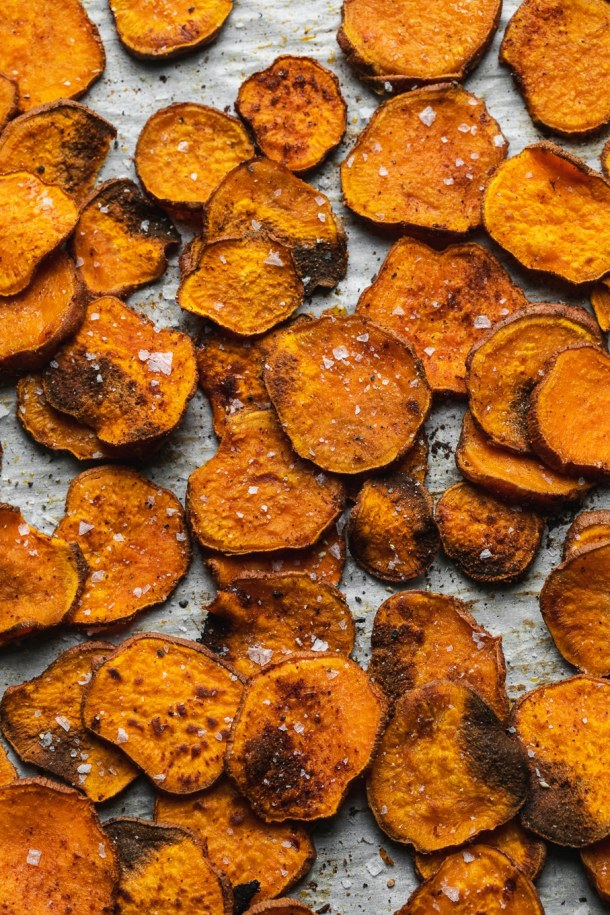 Overhead close up shot of thinly sliced baked sweet potatoes