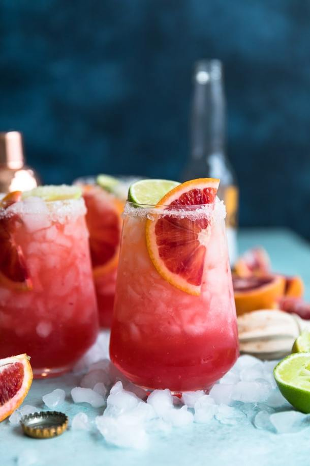 Forward facing close up shot of three blood orange beergaritas with a beer bottle against a dark blue background