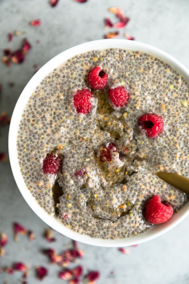 Bowl of chia pudding with honey being stirred into it with raspberries and chopped pistachios, with dried rosebuds scattered around the bowl