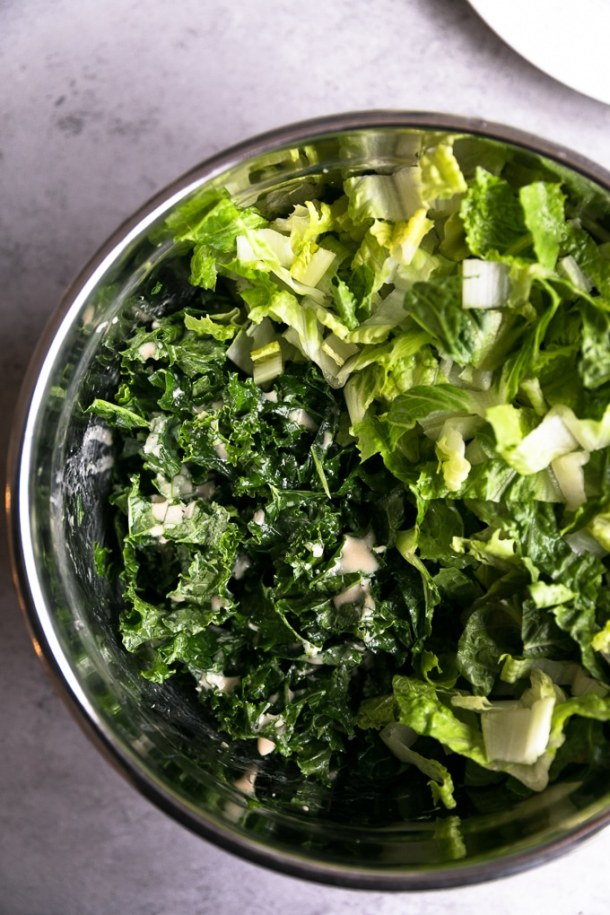 Overhead shot of a bowl of chopped romaine and kale with caesar dressing drizzled on it