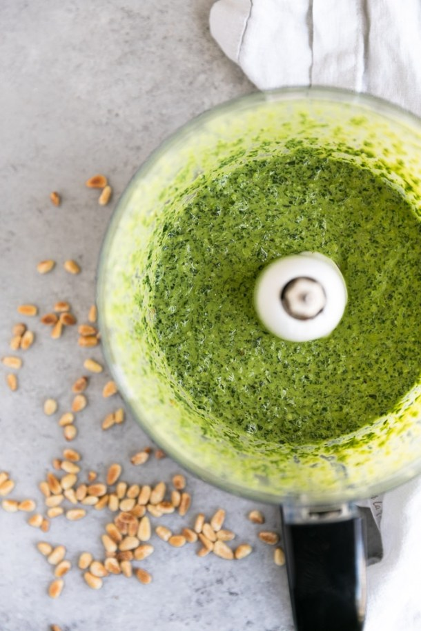 Overhead shot of a food processor filled with pesto and toasted pine nuts scattered alongside it