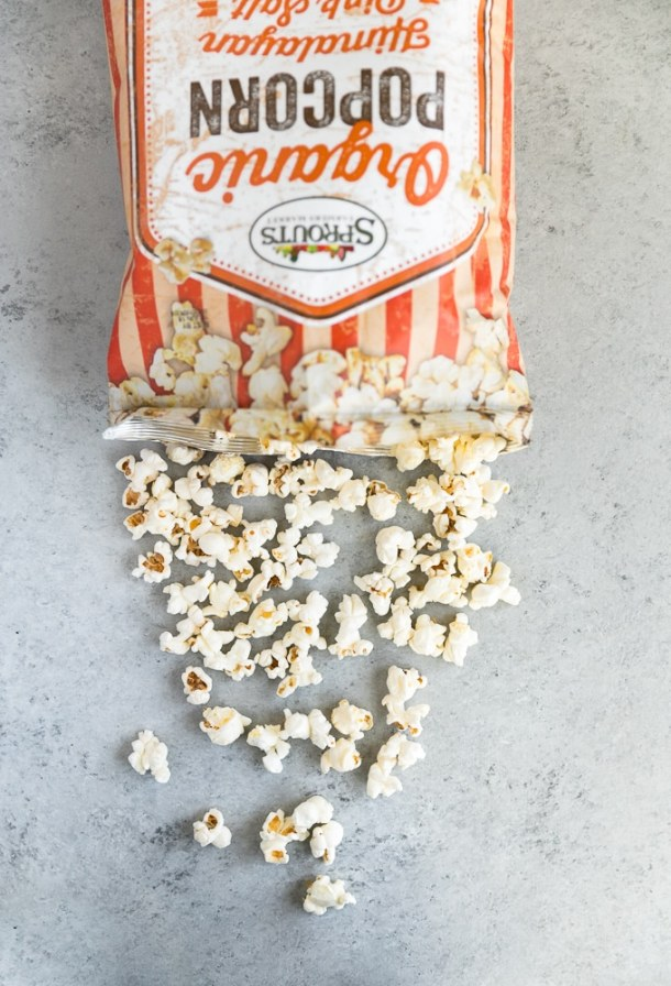 Overhead shot of a bag of popcorn with the popcorn pouring out