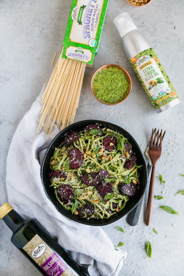 Overhead shot of a bowl of pesto pasta with roasted beets, and a box of pasta, a bowl of pesto, and a can of olive oil spray above it