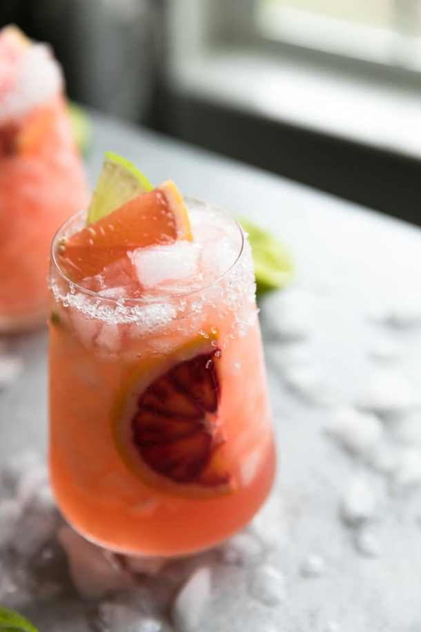 Close up shot of a cocktail with a blood orange slice in it, and a grapefruit slice and lime slice on top