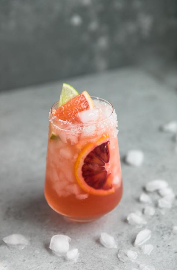 Close up shot of a cocktail with a blood orange slice in it, and a grapefruit slice and lime slice on top with crushed ice scattered around