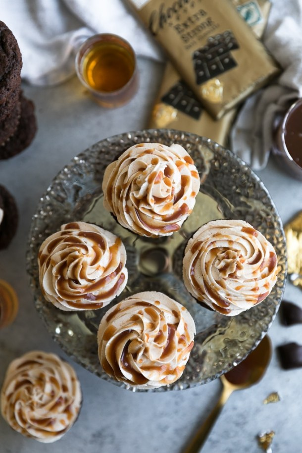 Overhead shot of four cupcakes on a cake stand surround by bars of chocolate, a shot of whiskey, and a glass of caramel sauce