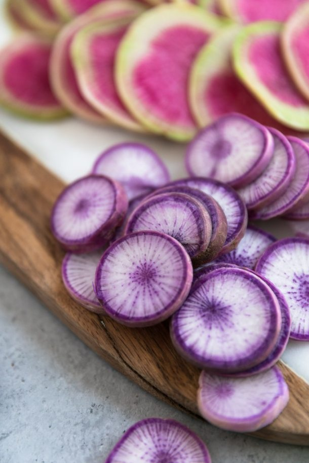 Close up shot of purple daikon radishes and hot pink watermelon radishes on a marble and wood board
